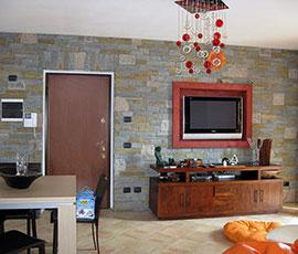 Rivestimento in pietra di Luserna con inserti in granito bianco e rosa con riquadro TV in muratura
